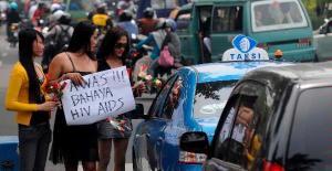 Sejumlah waria yang tergabung dalam Gerakan Waria Indonesia (GWI) menggelar aksi damai dengan membagikan bungan mawar di perempatan Jalan Raya Darmo dan Jalan Diponegoro, Surabaya, Rabu (1/12/2010). Mereka mengingatkan pengguna jalan tentang bahaya HIV/AIDS dan tidak sembarangan berhubungan seksual.